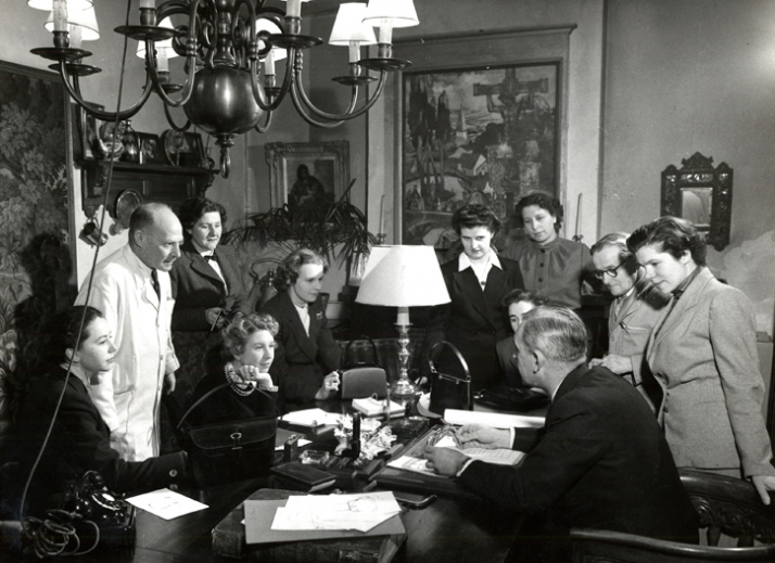 Delvaux employees, headed by Franz Schwennicke, discuss designs for the new collection. This 1950s image was used as part of an advertising campaign a