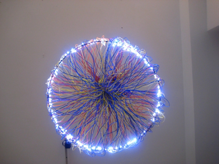 Wire Chandelier // Rainbow ribbon cable lights up. 300 individual hand soldered resin covered LEDs light up this chandelier. The color coded electrica
