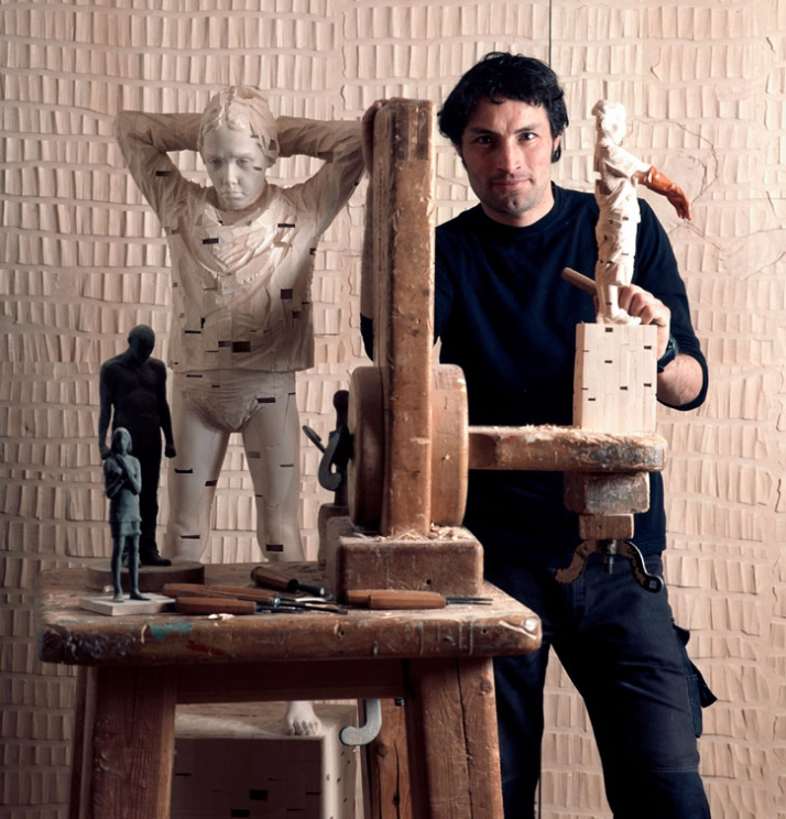 "The artist in his studio between: ""Just one step behind"", © Gehard Demetz, 2007, wood, 160 x 40 x 40 cm (on the left) and ""Everything he lied was true"