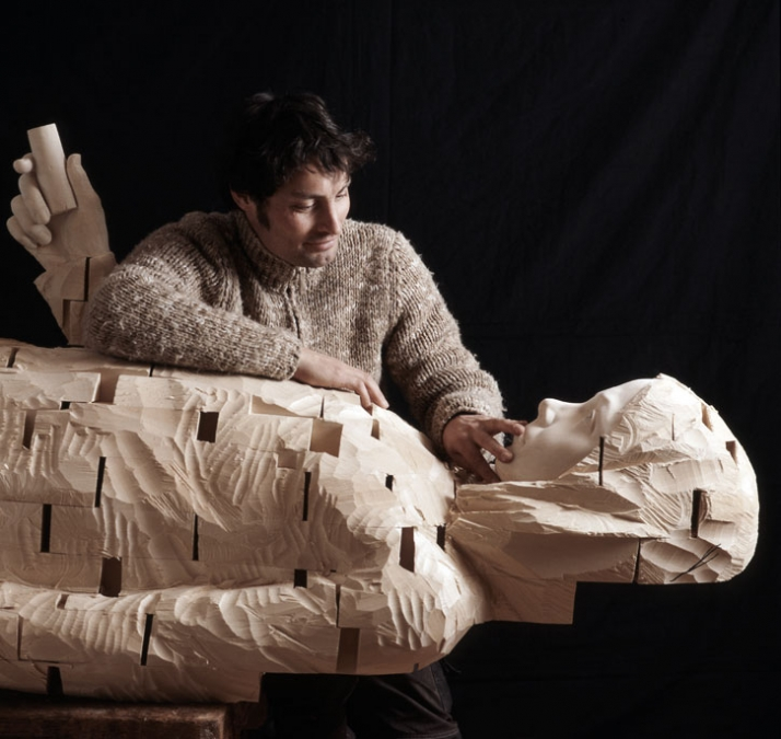 """The artist in his studio with the sculpture: """"I want to be flexible"""", © Gehard Demetz, 2007, wood, 320 x 79 x 87 cm Courtesy Galleria Rubin, Milano Ph"""