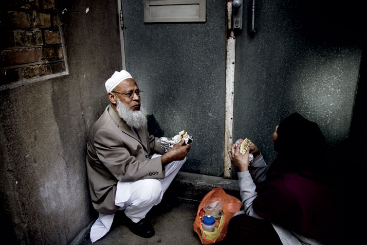 September 2011 // A man and woman eat lunch in a doorway off a side street in Shoreditch.photo © Brian Leli