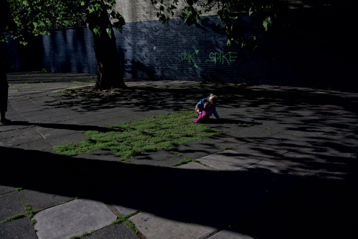June 2012 // A child crouches down in a patch of grass near the Old Street roundabout.photo © Brian Leli