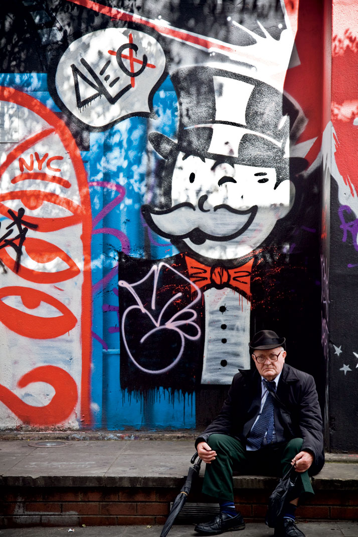 August 2011 // A man rests in front of a wall painted with street art at the Notting Hill Carnival. photo © Brian Leli