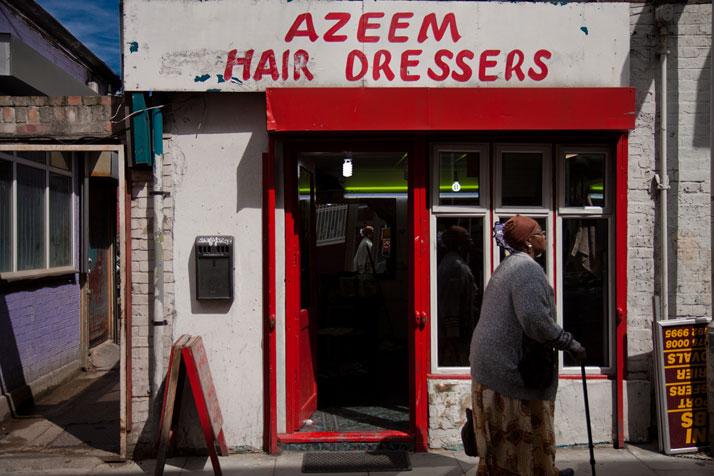 August 2012 // A woman walks past a barbershop toward Whitechapel Road in the Tower Hamlets borough.photo © Brian Leli