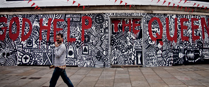 June 2012 // A man walks past a wall covered in street art during the Queen's Diamond Jubilee.photo © Brian Leli