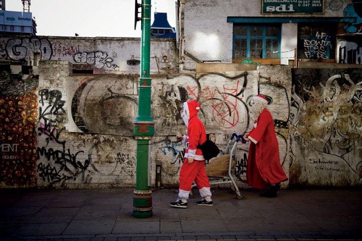December  2011 // Men in Santa Claus outfits walk with a shopping cart along  Brick Lane after SantaCon: 'a non-profit, non-political, non-religious