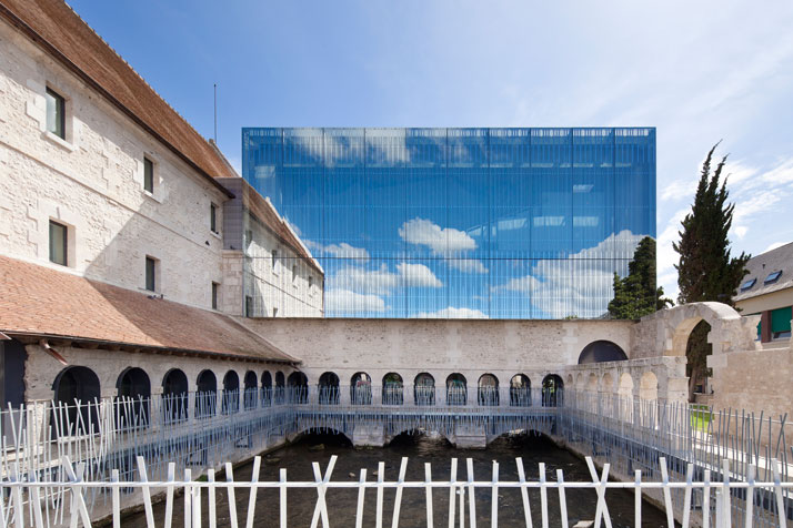 A semi-transparent and reflective façade allows the building to exploit its surrounding heritage.photo © Opus 5