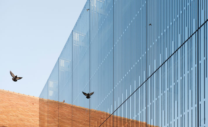 The glass panels intersect the old building, exposing the surroundings through its mirrored qualities.photo © Opus 5