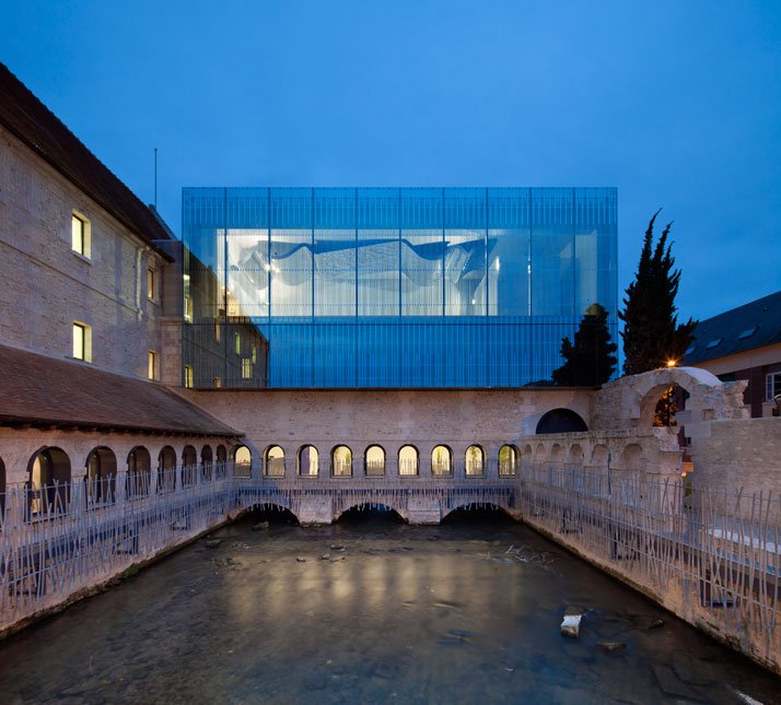 The news south-facing glass façade sits atop the former seventeenth century convent.