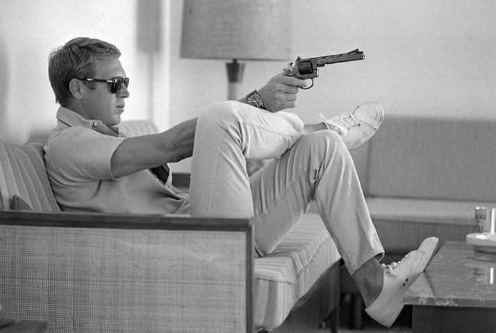 Steve McQueen: KING OF COOLSteve McQueen aims a pistol in his living room, CA, 1963photo © John Dominis / Time Inc. All Rights Reserved.