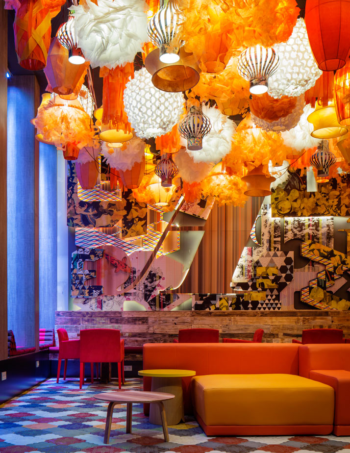 Generator BARCELONA.300+  lanterns in the hotel's lobby set the stage for a party atmosphere.   The spirit is heightened by the mix of Tres Tintas wallpaper, reclaimed   wood panels, Ivanka Flaster floor tiles and orange tone-on-tone   furnishings.Photo © Nikolas Koenig.