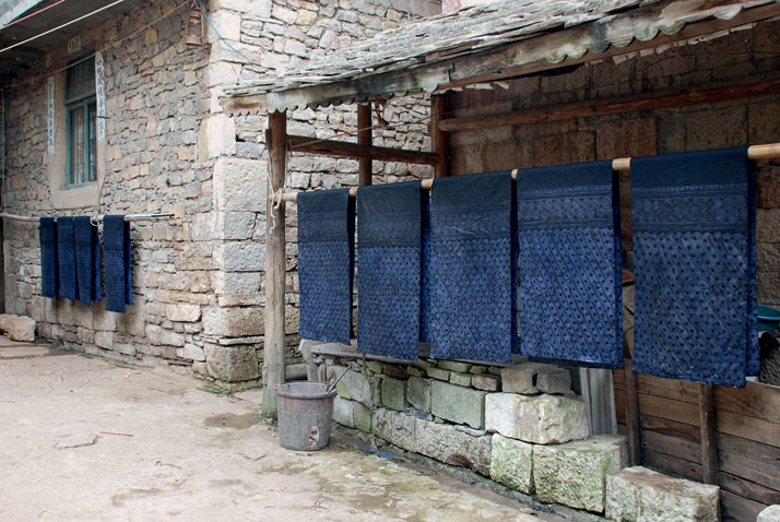 Skirt panels drying under the awning of a house in the Bouyi village of Shitou Zhai, China.'Indigo: The Colour That Changed the World', photo © Catherine Legrand / Thames & Hudson.