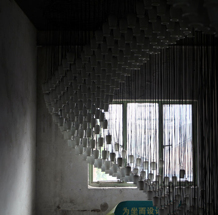 Milkywave by AIDIA STUDIO. It consists of 1664 reused glazed ceramic yoghurt bottles reconstituted into a looping wave of light.  Although this instal