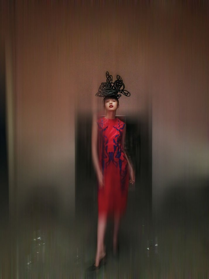 Hat: Philip Treacy and Simon Periton, A/W 1999. Cut out anarchy symbol  hat, foam. Dress: Tristan Webber, S/S 2000. Red silk dress with blue  appliquéd leather detailing, silk and leather. Shoes: Manolo Blahnik. Model: Xiao Wen Ju at IMG.photo © Nick Knight.