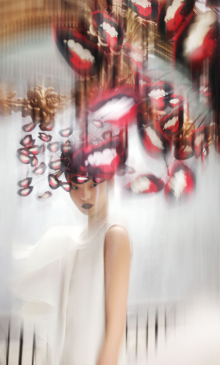 Hat: Philip Treacy, S/S 2003. Cut out mouths pop art hat, paper, silk and  wire. Dress: Chalayan, S/S 1999. Cream folded pleat dress, silk. Model:  Xiao Wen Ju at IMG. photo © Nick Knight.