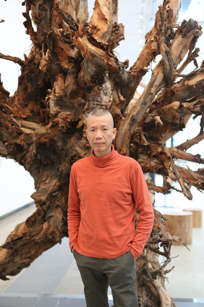 Cai Guo-Qiang in front of installation Eucalyptus at the Gallery of Modern Art, Brisbane, Australia, 2013.Photo by Yuyu Chen, courtesy Cai Studio. 蔡国强站在裝置作品《桉樹》前,布里斯班現代美 術館,澳洲,2013 年陳昱羽摄,蔡工作室提供