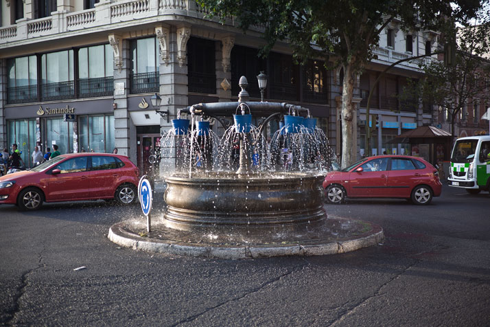 Installation of buckets with holes over a public Fountain which alter the water´s expected direction and sound. Madrid, Spain. Photo © SpY.