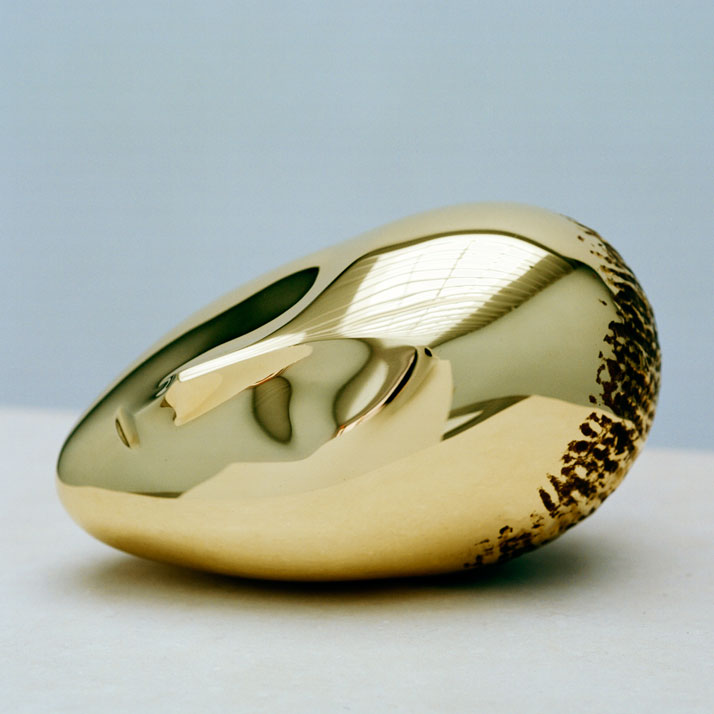 Constantin Brancusi, La Muse Endormie, 1923-2010, polished bronze, 7 3/8 x 10 1/4 x 6 1/8 inches, edition of 8. Photography by Francois Halard/© Artists Rights Society (ARS) New York/ADAGP, Paris. / Courtesy of the Brancusi Estate and Paul Kasmin Gallery.{Sleeping Muse II (1923), whose first version attracted the most attention in 1913, resulted in his first requests from collectors for bronze editions. It features also an abstracted face of a woman, like Mademoiselle Pogany II's serpentine figure beckons the viewer with her subdued look. Sleeping Muse II transforms the viewer into a voyeur watching over the sleeping woman with delicate suggestions of a nose, large oval-shaped closed eyes, and a half-open mouth.}