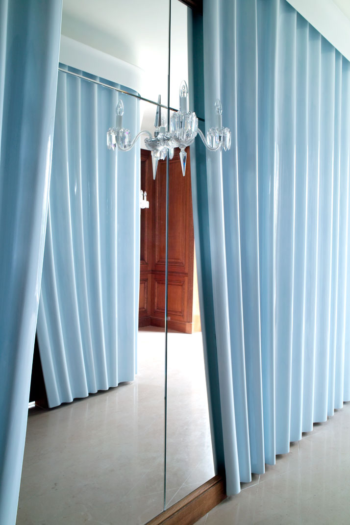Curtains made of lacquered plaster cover the walls of the main entrance; the curtains' pleats were hand-drawn by Fischler and then molded by an expert team of artisans. The painted mirror on the wall conceals a coat closet.Photo © Paul Graves for AD Magazine.
