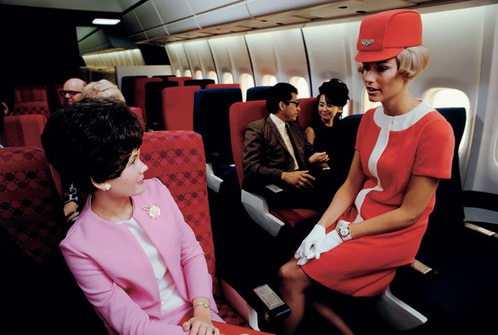 A United Airlines stewardess chats to a passenger in a simulated cabin of a Douglas DC-10, 1968.Airline: Style at 30,000 Feet (mini edition). Courtesy of Laurence King Publishing.