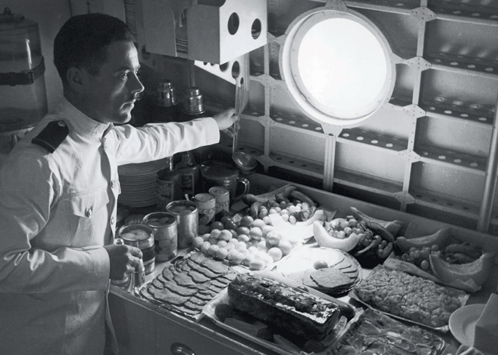 Spam and other assorted cold meats are accompanied by tinned vegetables and fresh fruit on board a BOAC Sunderland flying-boat bound for India from Hythe in the port of Southampton, UK, 1945.Airline: Style at 30,000 Feet (mini edition). Courtesy of Laurence King Publishing.