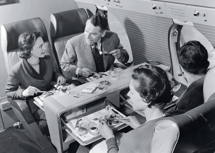 Lunch in first class on board a BEA Vickers Viscount, 1953. Flying was still a luxurious mode of transport, with space for congenial eating and seating arrangements; one could also enjoy an after-dinner smoke.Airline: Style at 30,000 Feet (mini edition). Courtesy of Laurence King Publishing.