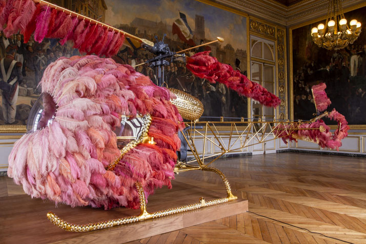 Joana Vasconcelos, Lilicoptère, 2012.Bell 47 helicopter, ostrich feathers, Swarovski crystals, gold leaf, industrial coating, dyed leather upholstery embossed with fine gold, Arraiolos rugs, walnut wood, wood grain painting, passementerie.300 x 274 x 1265 cmCourtesy Haunch of Venison/Christie's, London.Work produced in collaboration with Fundação Ricardo do Espírito Santo Silva, Lisbon.2012 Joana Vasconcelos Versailles, Château de Versailles, Versailles, photo © Joana Vasconcelos.