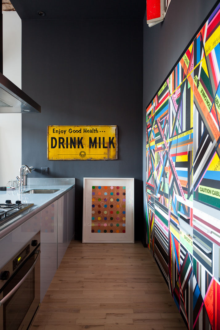 A Damien Hirst painting leans casually against the kitchen wall. The cupboards were covered with adhesive tape patterns by Houssein. Photo © Fran Parente.