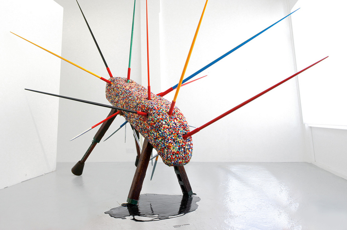 Fantich & Young, Mascot, 2012. Sculpture dimentions: (H) 310cm x (W) 380cm x (L) 415cm. Materials: Vaulting Horse, Military Medals Ribbons, Junior Sport Javelins, Crude Oil. Photo © Fantich & Young.