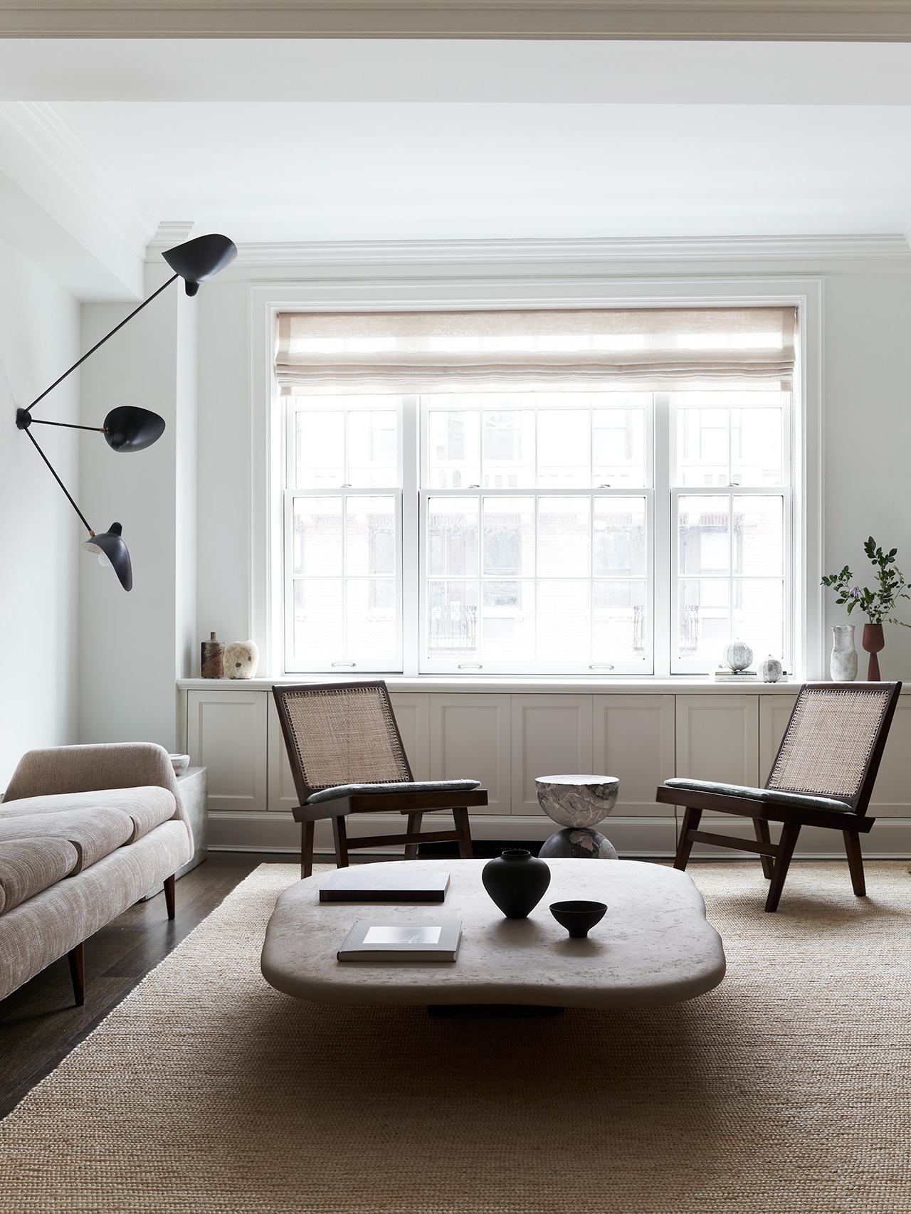 Photography by Adrian Gaut. Styling by Colin King. Featured: Coffee table by Axel Vervoordt; Pair of chairs by Pierre Jeanneret circa 1958 from Dobrinka Salzman; Wall sconce by Serge Mouille circa 1955 from MDFG; Bespoke side table by Sandra Weingort for Light on White.