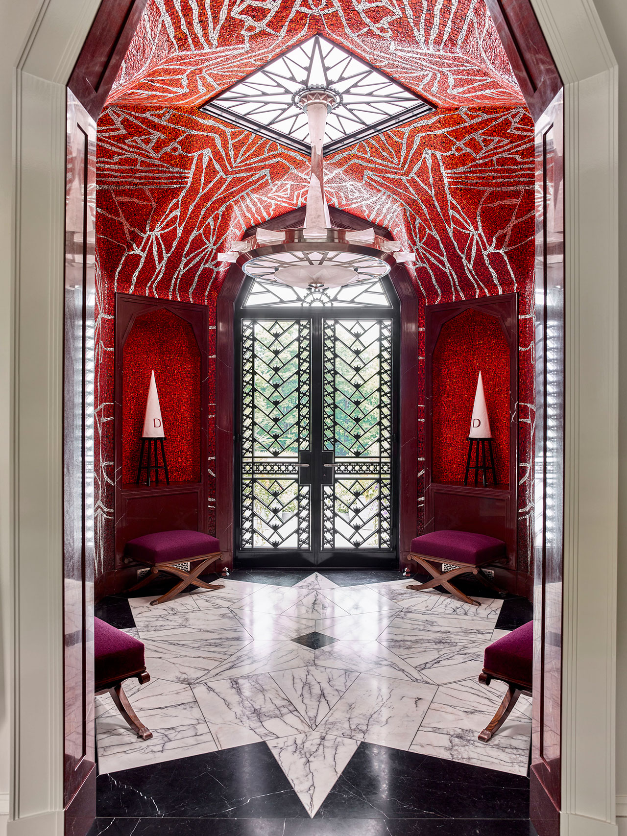 Entrance Hall: A nickel and cast-glass chandelier by Todd Anderson centers the octagonal space. The black-and-white marble floor tiles are laid in a geometric pattern. X-form stools by Émile-Jacques Ruhlmann (ca. 1928) sit underneath the red Laguna marble–framed niches. The front door's black steel grilles are ornamented with sunrise motifs and automotive gears. Photography by Eric Piasecki.