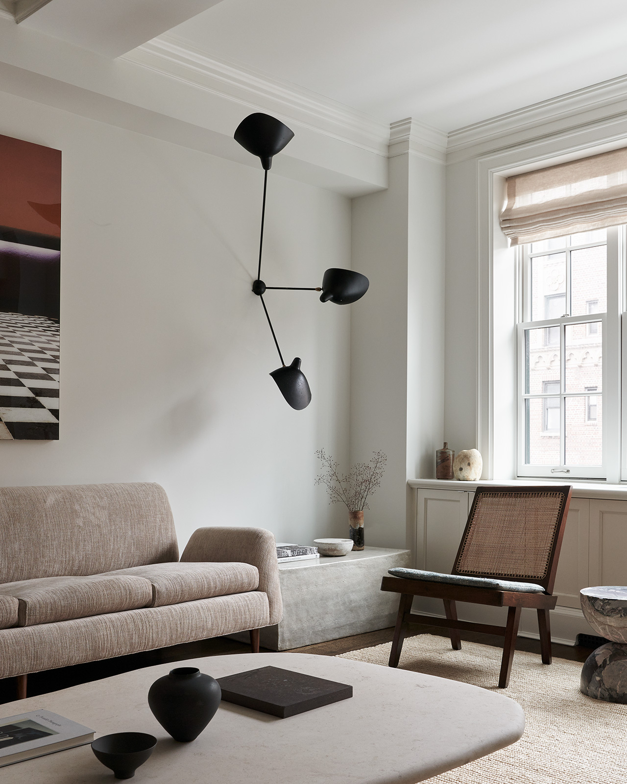 Photography by Adrian Gaut. Styling by Colin King. Featured: Sofa by Martin Eisler & Carlo Hauner for Forma circa 1955 from Bossa Furniture; Coffee table by Axel Vervoordt; Pair of chairs by Pierre Jeanneret circa 1958 from Dobrinka Salzman; Wall sconce by Serge Mouille circa 1955 from MDFG; Bespoke side table below sconceby Sandra Weingort fabricated by William Coggin from Studio Tashtego.