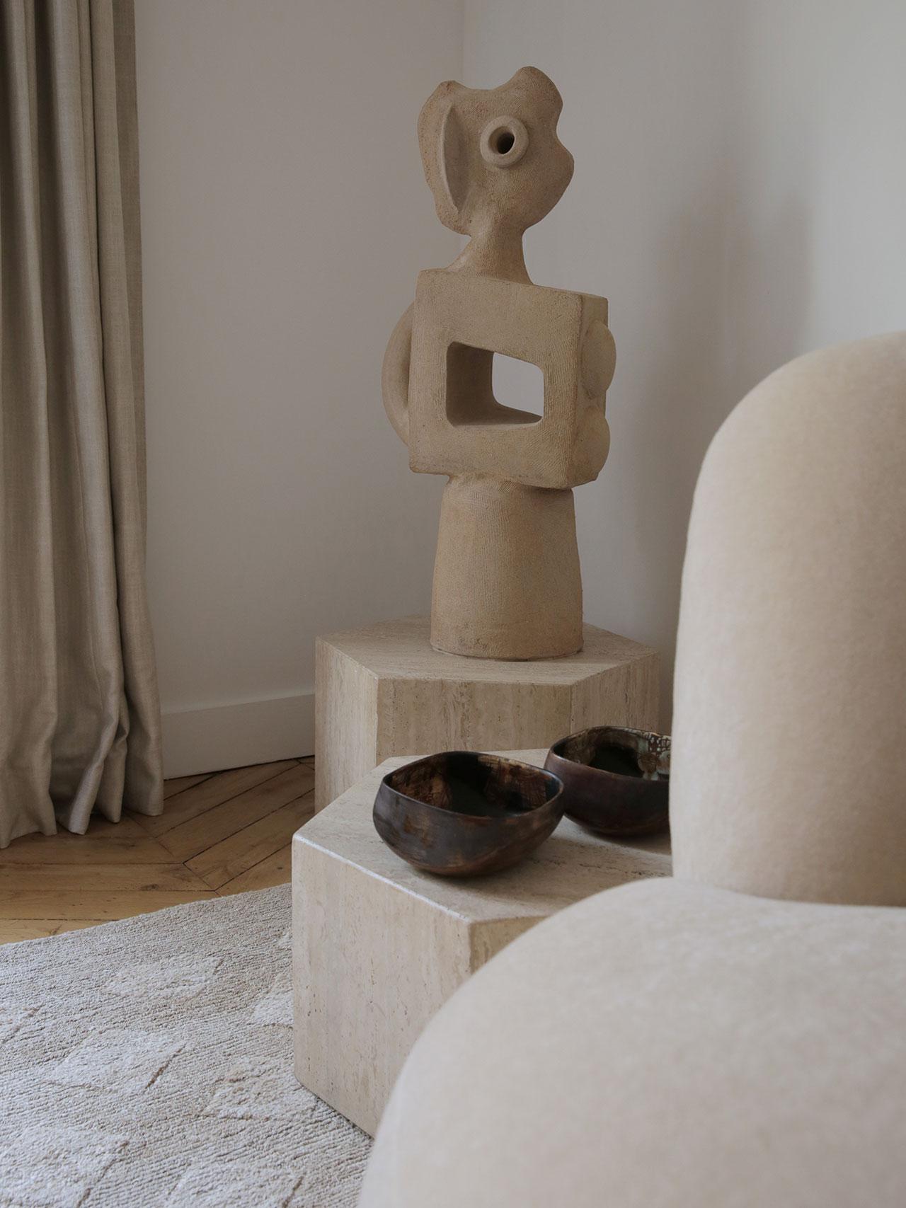 Monumental sculpture in stoneware by Michel Lanos (1926 - 2005), 1990-2000. Setof 3 hexagonal side tablesin travertin by unknown designer, circa 1970-1980. Pair of bowlsin ceramic by Eugène Fidler, 1970. Photography by Damien de Medeiros.