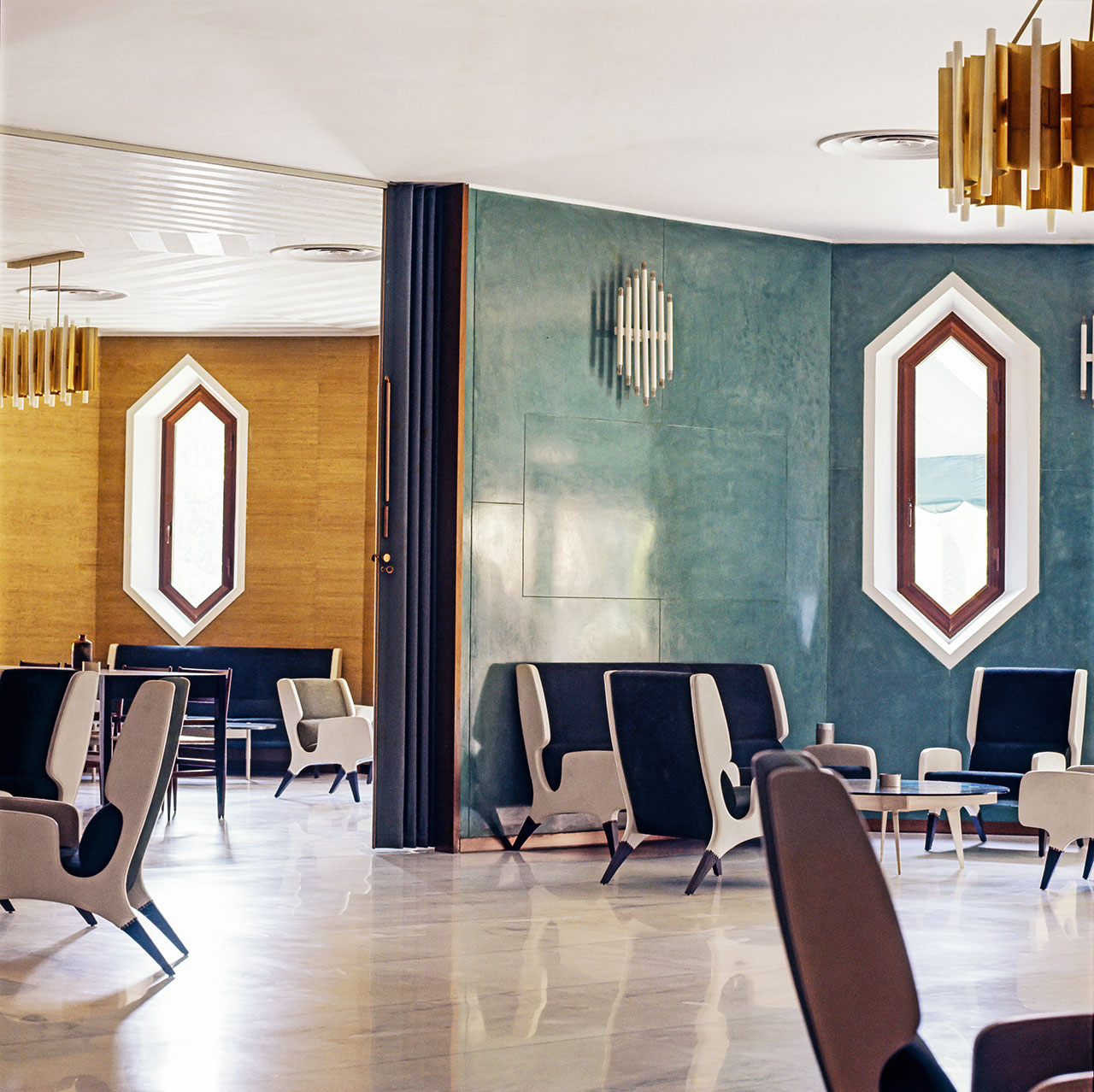 "Hotel Parco dei Principi, Rome, 1961–64. View of the lobby. The walls are covered with ""Grass Cloth"" wallpaper by Braendli and teal-green ""Sigmulto"" stucco by Sigma. The space is furnished with armchairs and sofas (model 899) and coffee tables produced by Cassina. Wall sconces and ceiling lights were designed by Ponti with Emanuele Ponzio, realized by Candle, 1960. The hexagonal bronze window frames were manufactured by the Del Vecchio factory of Fano. Photo © Gio Ponti Archives/ Historical Archive of Ponti's Heirs."