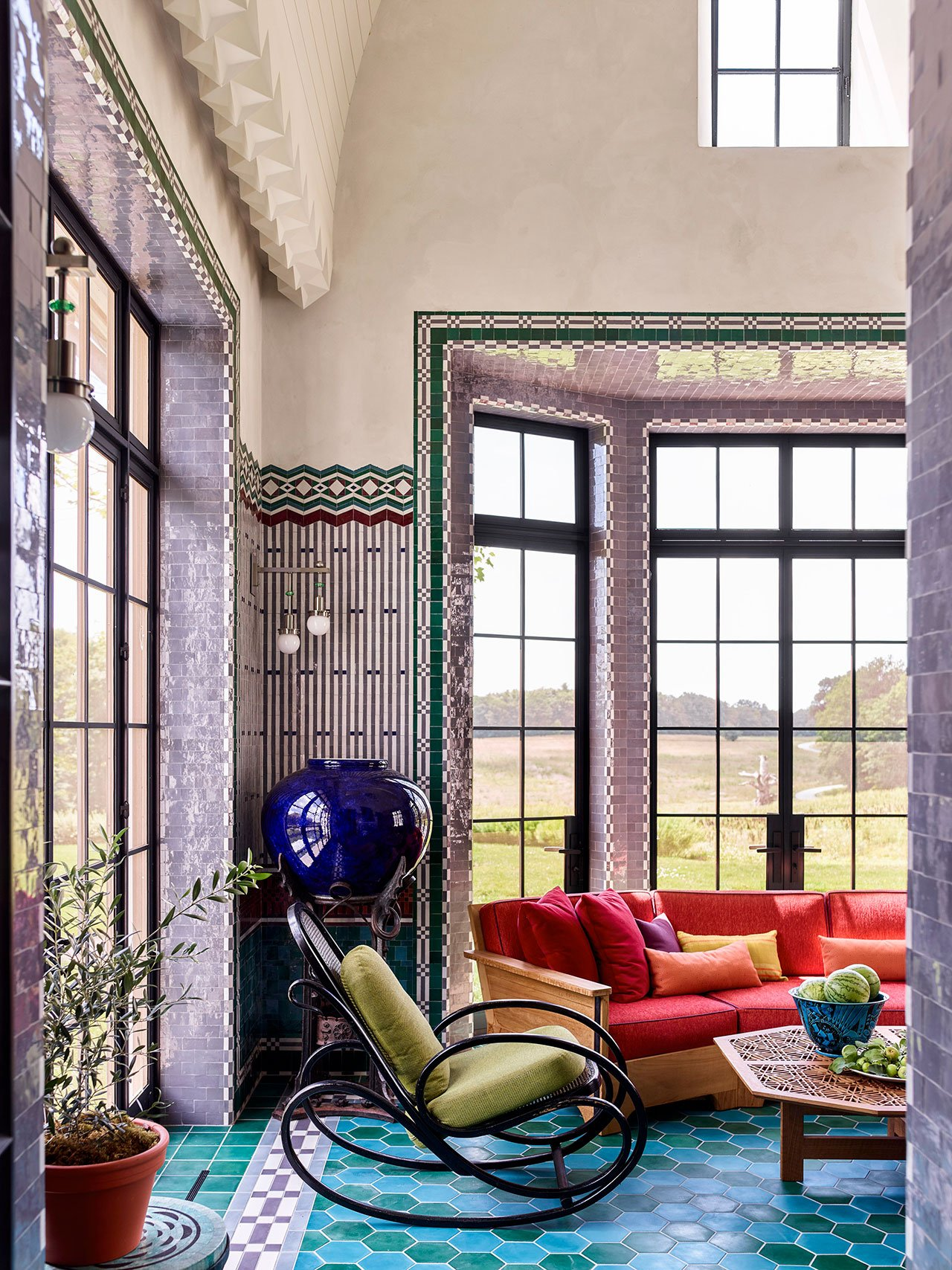 The walls of the screened porch are clad in green, burgundy, gray, and purple Moroccan zellige tiles in patterns inspired by the work of Koloman Moser and Joseph Urban. Photography by Eric Piasecki.