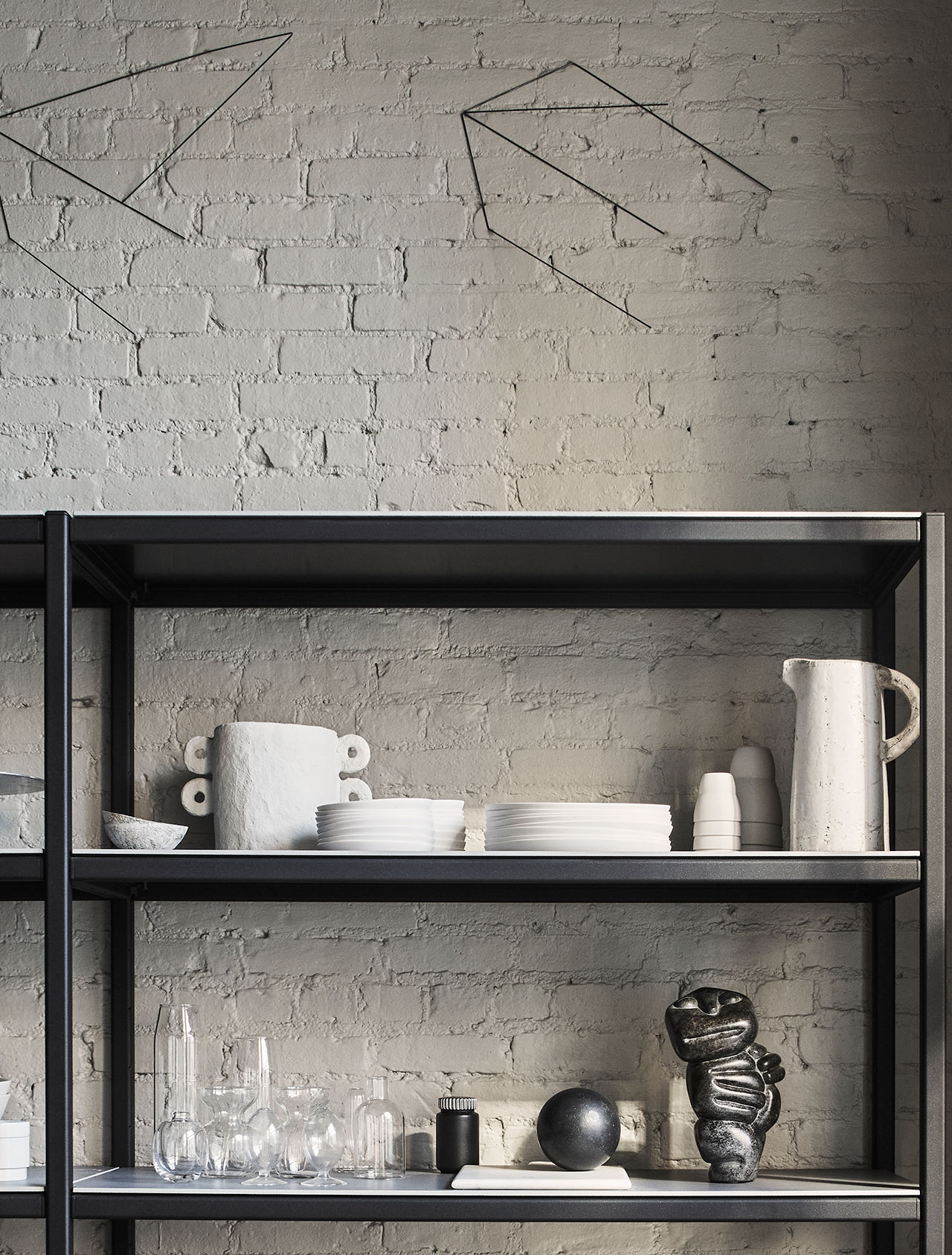 """Photography by Adrian Gaut.Styling by Colin King. © Vipp Featured:Vipp Tall Racks, Vintage glass, Vipp ceramics, Black solid iron sphere by artist Sofie Østerby, Metal art installations above the rack by Lawrence Kenny, Farrow & Ball """"Drop Cloth"""" paint."""