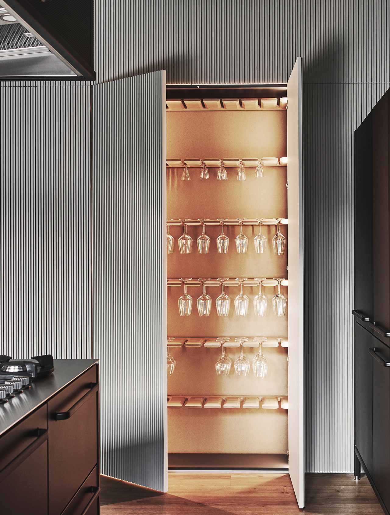 Photography by Adrian Gaut.Styling by Colin King. © Vipp Featured:Interior details of the Elie Chaker millwork. The custom wine glass storage was designed by Sofie, Frank, and Raëd Abillama Architects. Extruded Aluminum cabinets.Kvadrat's Hero felt backing. Oak wine glass racks.