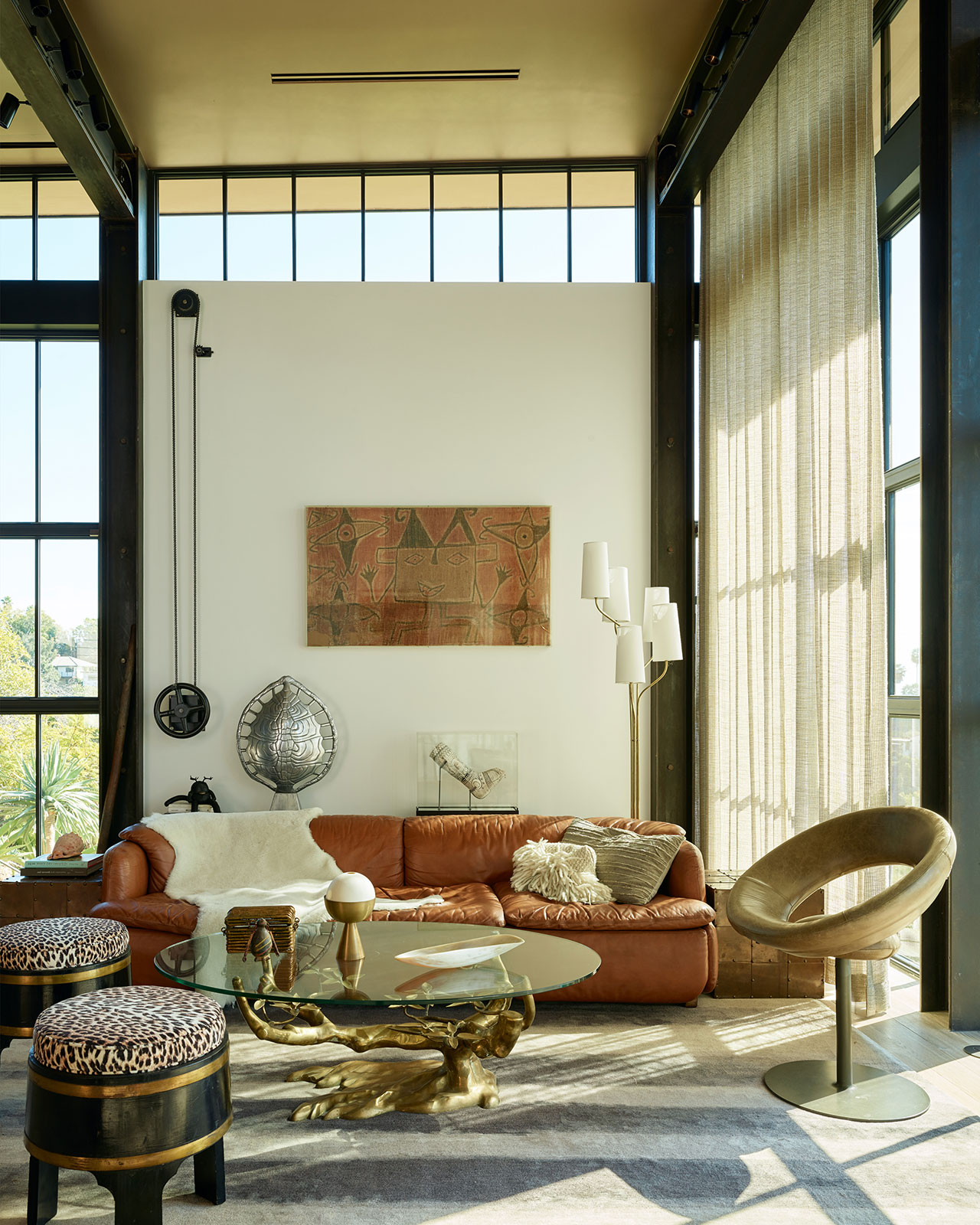 HollywoodHillsHouse by Mutuus Studio in Los Angeles, California.Photography by Kevin Scott. Featured:Willy Daro bronze table withcustom glass top, sofa byAlberto Rosselli for Saporiti,Anel chair byRicardo Fasanello, Japanese Barrel stools circa 1930 reupholstered,polished aluminum Tortoise shell lamp by Arthur Court,Brian Henson's cast with Jim Hensons cartoons, Aboriginal tapestry (on the wall).