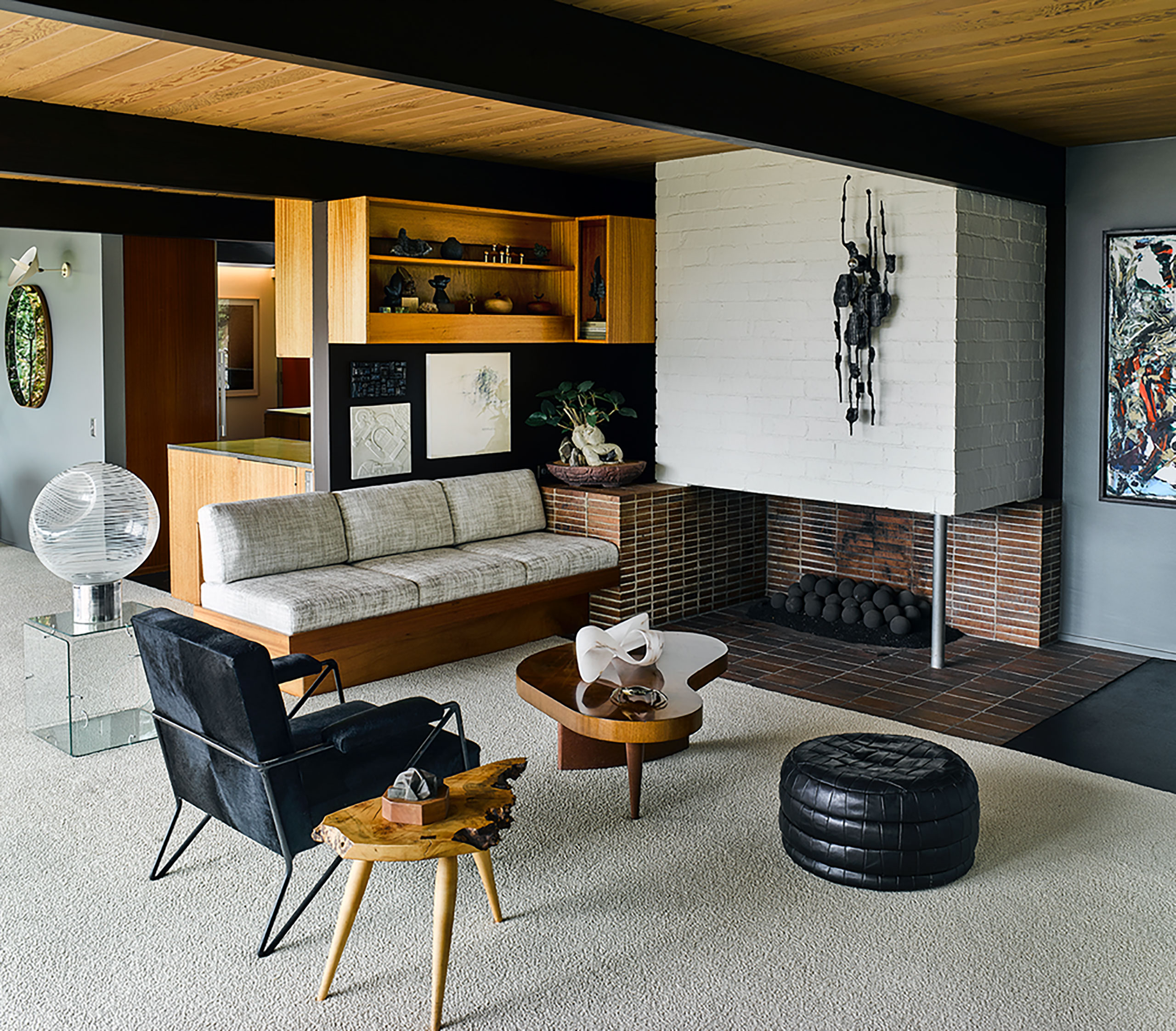 Photography by Douglas Friedman. Featured: Built-in sofa by Richard Neutra; Vistosi etched globe lamp on Gerard McCabe cube glass table; Black calf skin chair by Milo Baughman; drift wood side table by Michael Wilson; coffee table by Gilbert Rohde; leather patchwork ottoman by DeSede; bronze light sculpture by Tom Ahlstrom & Hans Ehrlich.