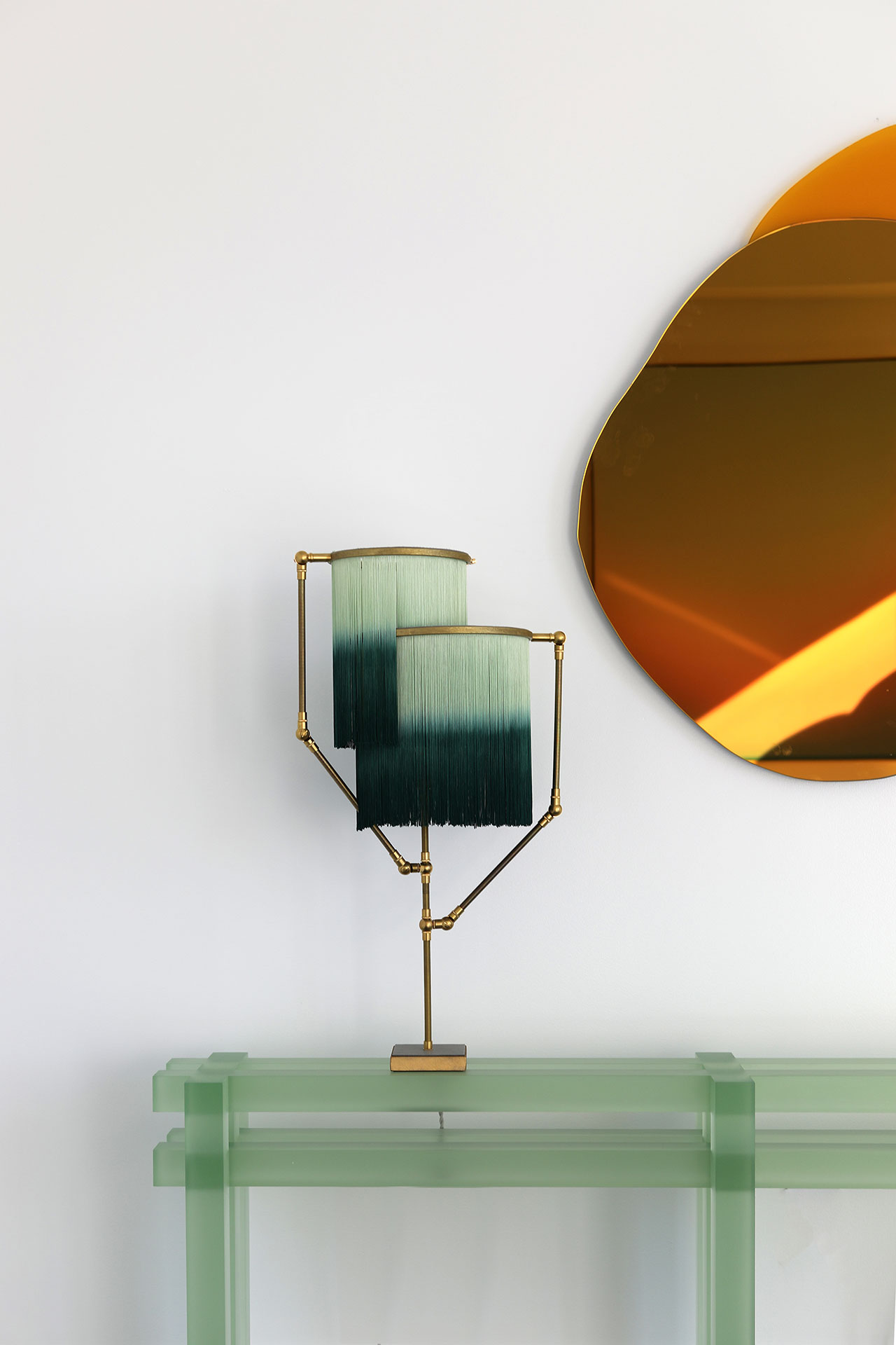 Galerie Philia at Walker Tower, Chelsea, New York. Courtesy of Galerie Philia. Featured:  Laurène Guarneri, Ombrée hand-sculpted mirror, 2020. Gold mirror, yellow glass. 85 x 100 x 1.3 cm. Sander Bottinga, Charme Table Lamp, 2019. Brass, Leather, Viscose, Wood. 73 x 38 x 25 cm.  Laurids Gallée, Green Console. Resin. 150 x 25 x 70 cm.