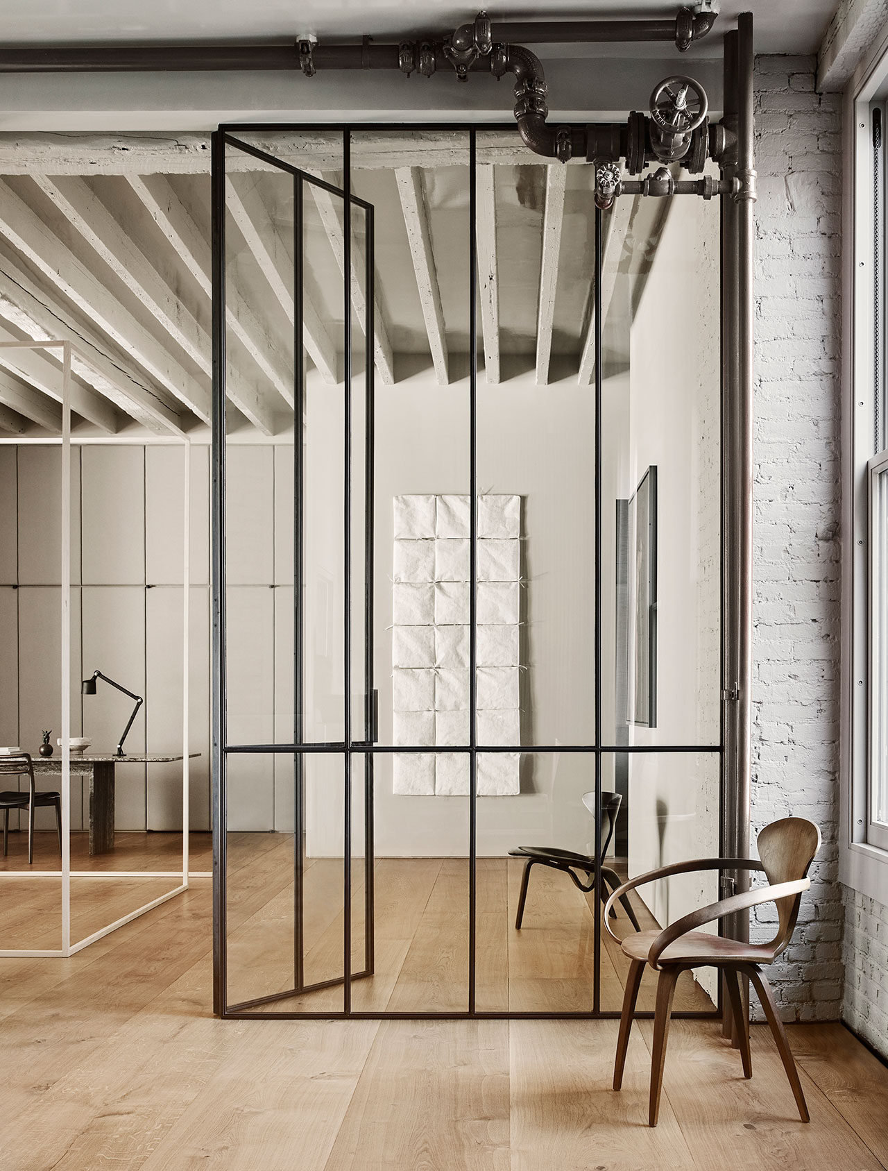 """Photography by Adrian Gaut.Styling by Colin King. © Vipp Featured: The custom glass partition, which was built in Beirut, lies between the master bedroom and the gallery, Cherner chair, Poul KjaerholmPK0 Chair, Farrow & Ball """" Drop Cloth"""" paint."""