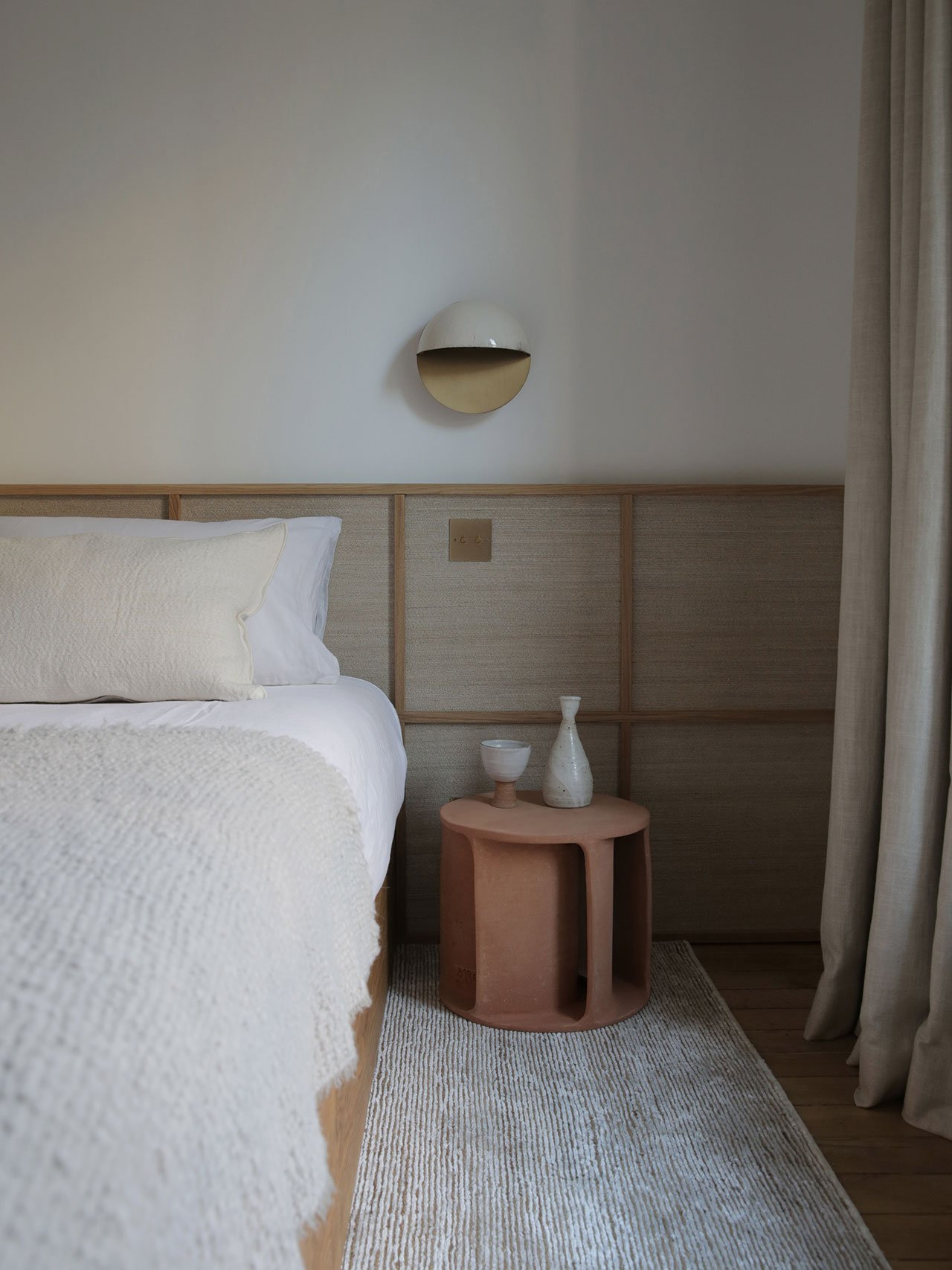 Bedhead in oak and thin rattan wallpaper by Emmanuelle Simon. Sconce in raku and brassby Emmanuelle Simon. Illuminated side table in in earthware by Guy Bareff. Photography by Damien de Medeiros.