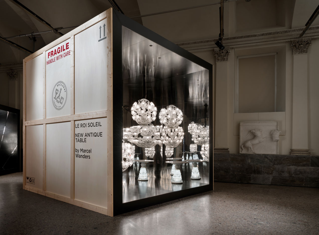 Lumières out of the box installation view atthe Fine Arts Academy of Brera featuringLe Roi Soleilspherical chandelier and New Antique side table byMarcel Wanders forBaccarat.
