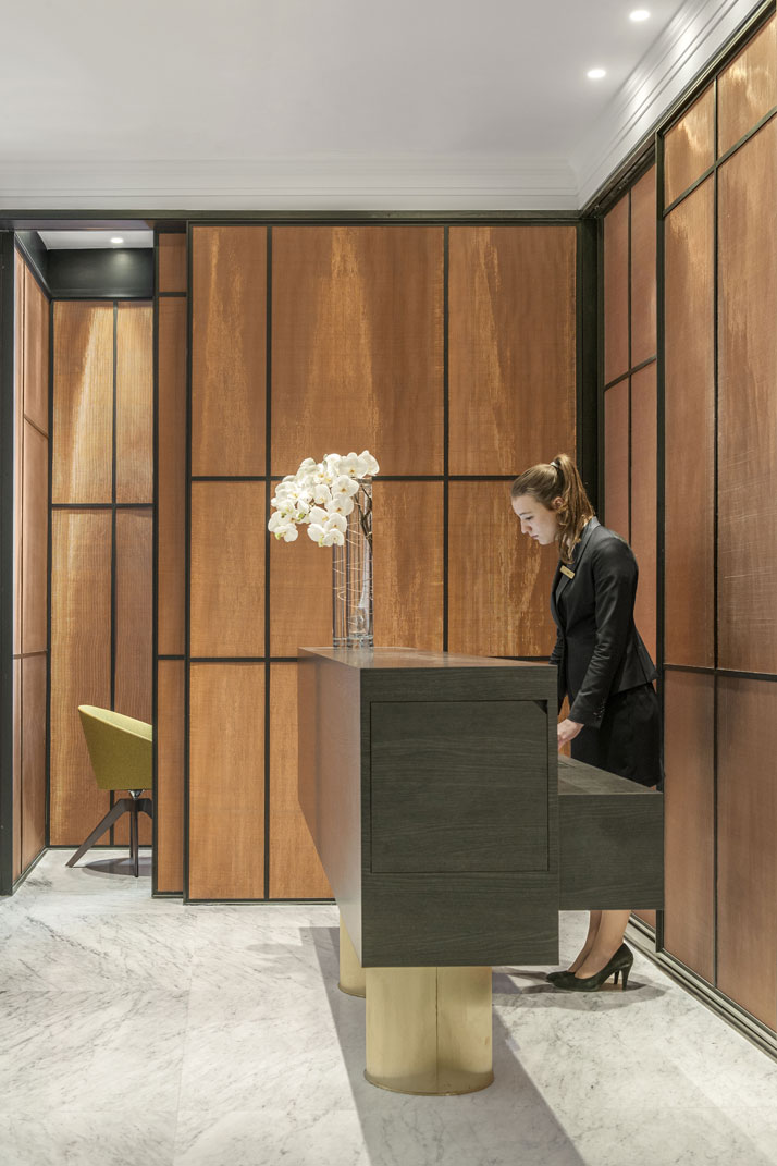 Reception desk in black oak resting on two brass pedestals, designed by François Champsaur and made by Gendre. Screen in brass mesh designed by François Champsaur and made by Gendre. Armchairs made by PHS. Photo © Hôtel Vernet, Paris, Champs-Élysées.