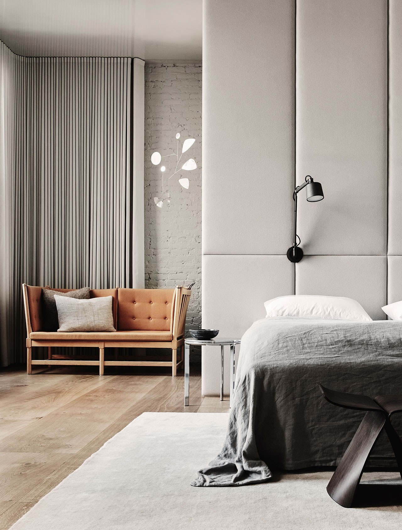 """Photography by Adrian Gaut.Styling by Colin King. © Vipp Featured: Børge Mogensen sofa with Raf Simons fabric, Upholstered fabric wall by Elie Chaker, Handmade silver mobile by Lappalainen, Vipp Wall Lamps, Hastens bed, Vipp Side Table, Vipp Rug, Sori Yanagi Stool, Farrow & Ball """"Hardwich White"""" paint."""