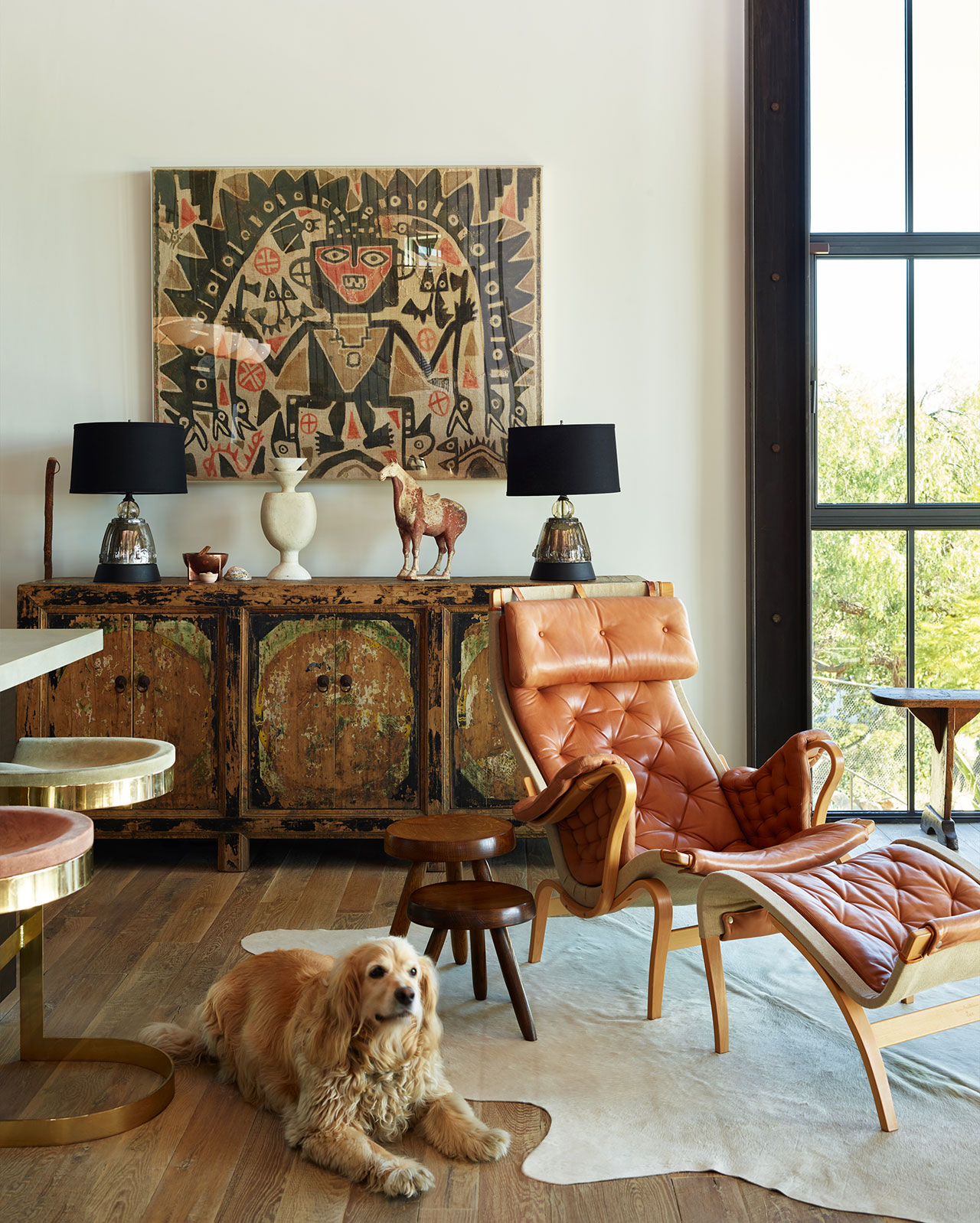 """HollywoodHillsHouse by Mutuus Studio in Los Angeles, California.Photography by Kevin Scott. Featured:Bruno Mathsson """"Pernilla"""" Lounge chair, vintage Warren Bacon Saddle stools, and Casper, the owners' dog."""