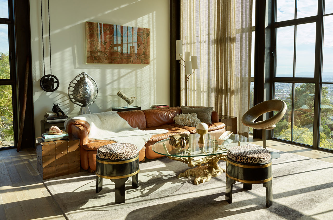 HollywoodHillsHouse by Mutuus Studio in Los Angeles, California.Photography by Kevin Scott. Featured:Willy Darobronze table withcustom glass top, sofa byAlberto Rossellifor Saporiti,Anel chair by Ricardo Fasanello,polished aluminum Tortoise shell lamp byArthur Court,Brian Henson's cast withJim Hensonscartoons, Aboriginal tapestry (on the wall).