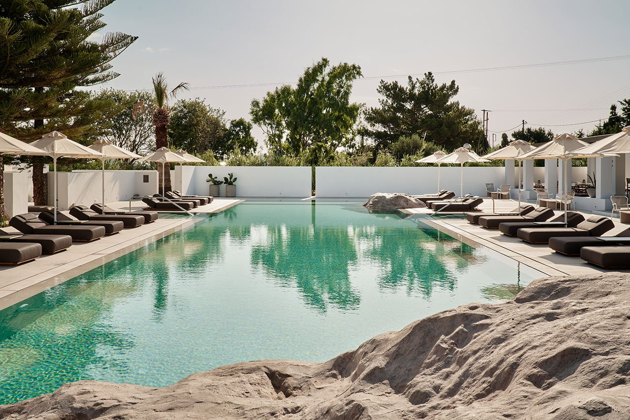 The cruciform pool is intercepted by rock formations echoing the local landscape. © Parīlio a member of Design Hotels™ | Kolympithres,Naoussa Paros, Greece.Photo by Claus Brechenmacher & Reiner Baumann. Courtesy of Parīlio.
