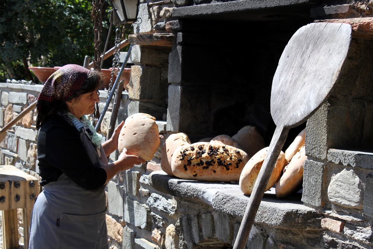 Baking country bread at Kinsterna's old stone oven. Photo © Kinsterna Hotel.