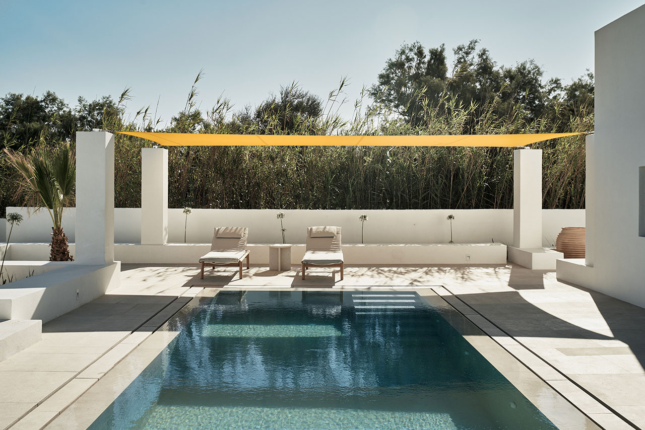Yellow parasols add accents of colour to the whitewashed architecture. © Parīlio a member of Design Hotels™ | Kolympithres,Naoussa Paros, Greece.Photo by Claus Brechenmacher & Reiner Baumann. Courtesy of Parīlio.